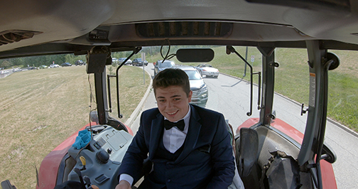 joey riding his tractor to his high school graduation